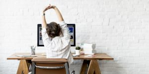 仕事の途中で伸びをする女性