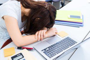 PCの前で寝る女性