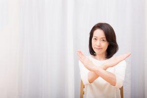 手を交差させる女性