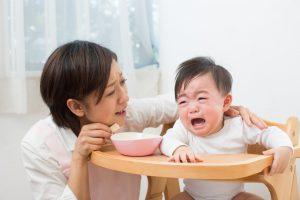 泣く赤ちゃんとあやす母親