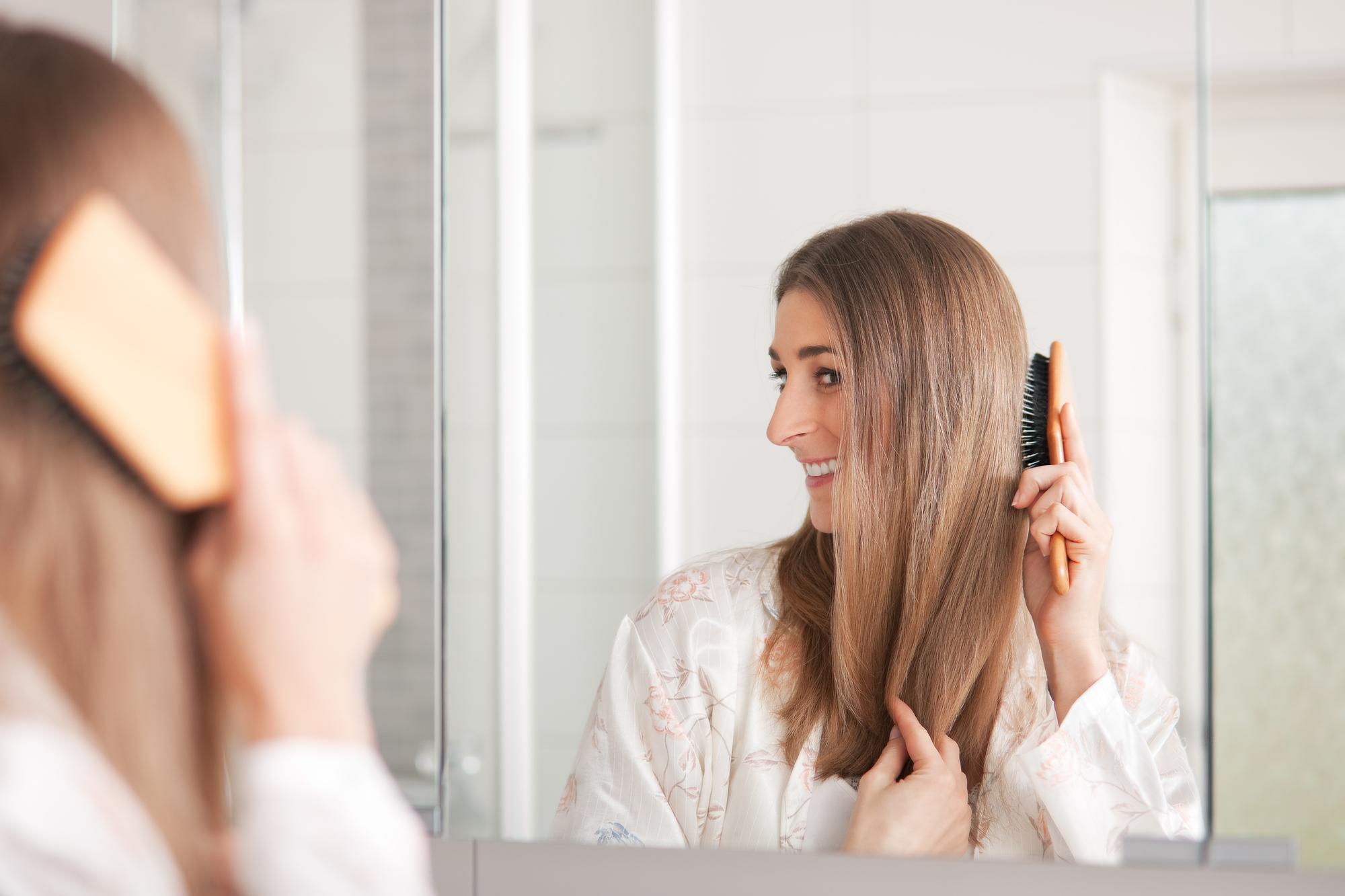 櫛で髪をとかす女性