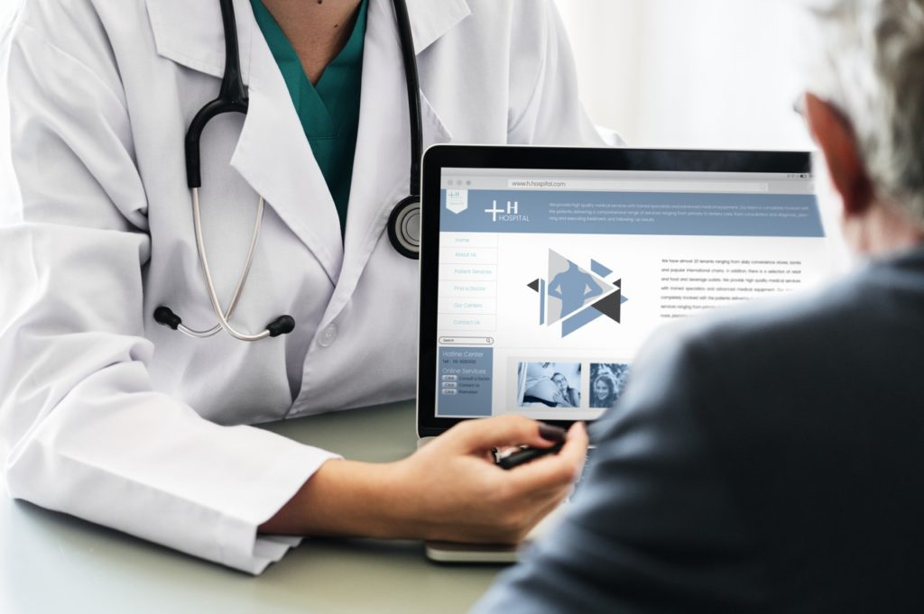 パソコンの画面を見せる医師
